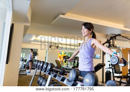 Woman lifting up dumbbell