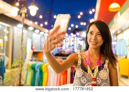 Young Woman taking selfie by cellphone at night market in Thailand