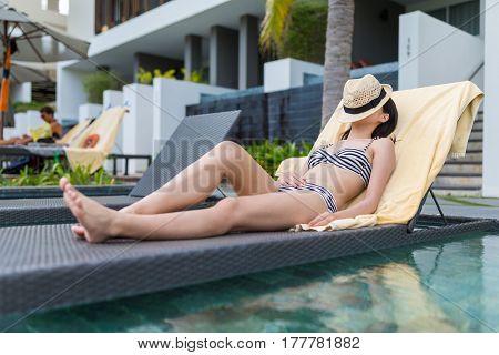 Young Woman enjoy sun bath in swimming pool