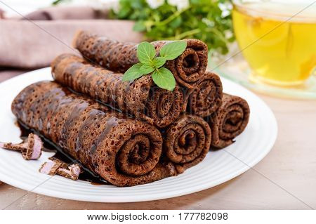 Thin delicate chocolate pancakes rolled laid out in a pile on a white plate and a cup of herbal tea with honey