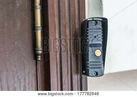 Modern door bell button on wall of house