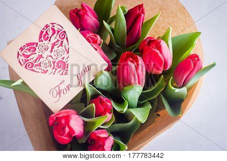 Bunch of Pink tulips on wooden table with paper card letter For You. Spring Flowers holiday Background. Easter or Mother Day Gift Present.