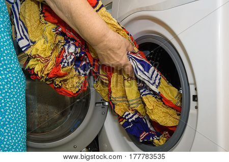 Close-up of young woman doing laundry at her home using washing machine