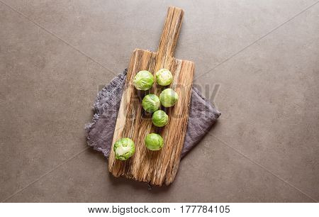 Fresh Brussels Sprouts On A Wooden Board. Dark Gray Background.