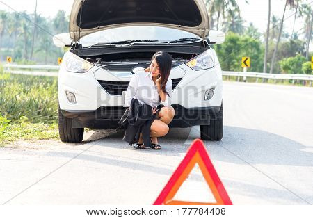 Business woman with a broken car calling for assistance