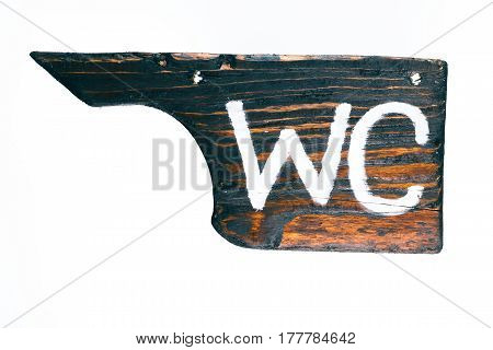 Signboard of old dark wood with text 'WC' isolated over white background. Close-up view