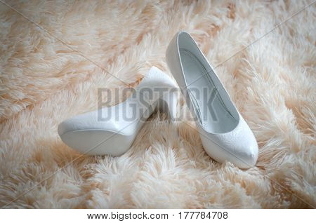 White wedding bride shoes high heel lay on a shaggy soft bright blanket