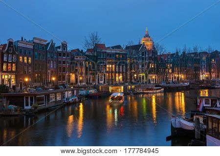 Canal in Amsterdam with houseboats  in the evening illumination, the Netherlands