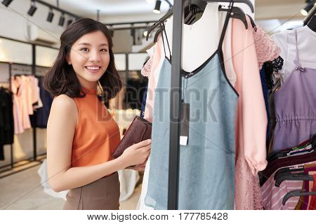 Attractive young woman choosing dress from new collection