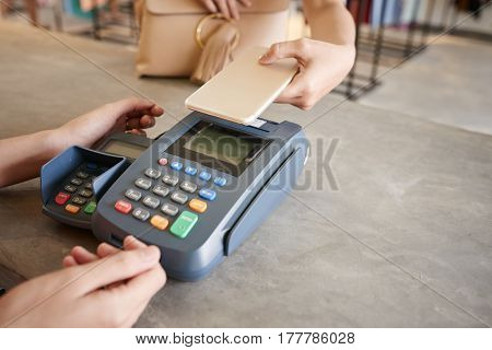 Close-up image of woman holding her phone over terminal to pay the bill