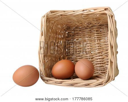 Two eggs in a basket and one separately isolated on white