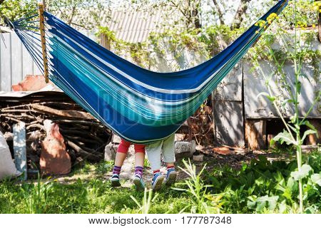 Children's feet in blue hammock on a background of nature greenery.