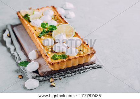 Tart with lime and lemon curd nut pistachios and meringue. Citrus cake. Horizontal image with copy space