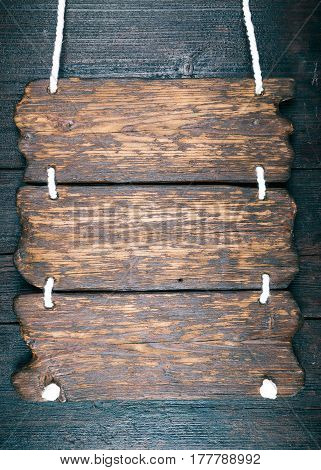 Signboard of old dark wood on wooden wall or door. Close-up view