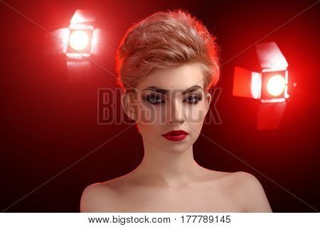 Beautiful features highlighted. Studio beauty shot of a gorgeous young blonde woman wearing professional makeup posing in red artistic lighting on dark background copyspace red lips smoky eyes beauty