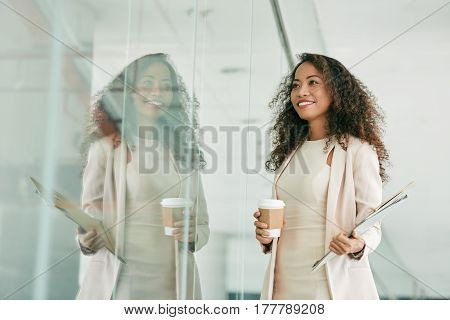 Smiling Asian female entrepreneur walking in office building