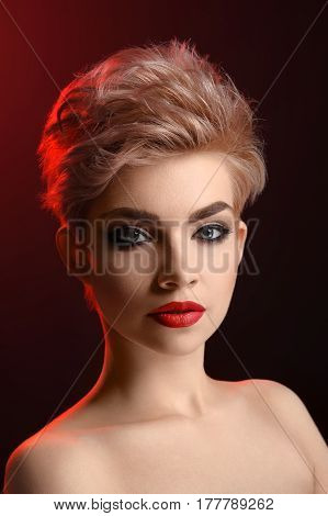 Fierce beauty. Vertical studio portrait of a beautiful young blonde haired woman with smoky eyes and red lips makeup looking confidently to the camera cosmetics visage fashion modeling concept