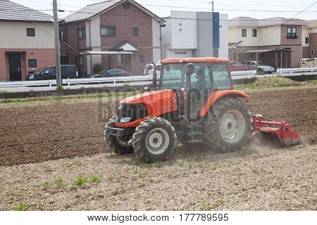 NAGOYA JAPAN - April 16, 2016: Farmer in tractor preparing land for sowing. Farmer in tractor preparing land with seedbed cultivator.