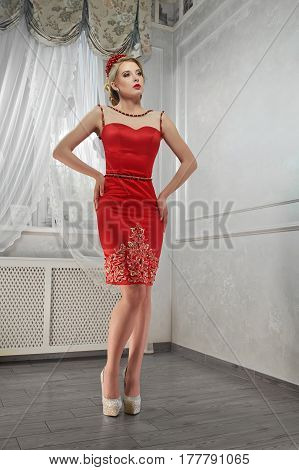 Young beauty woman, magnificent woman in red dress, on hills, hands on hips.