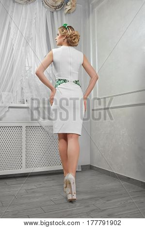 A beautiful woman, blond girl in a short white dress, on heels, hands on hips in a room.