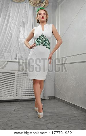 A beautiful woman, blond girl in a short white dress, on heels, hands on hips in a room, back view.