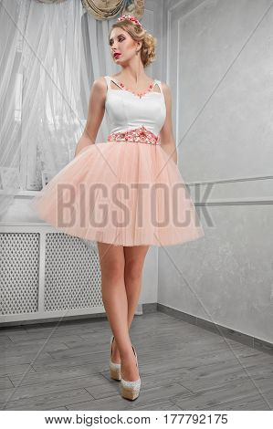 Young beautiful, pretty woman in light pink short dress with red embroidery, hands on hips on hills, full-length portrait in the room .