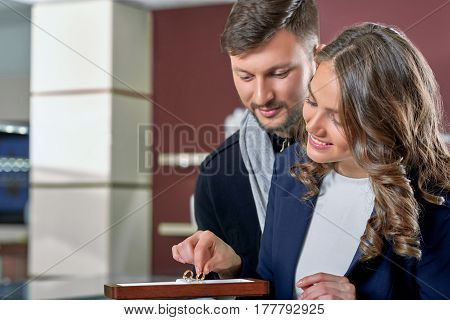 Golden elegance. Closeup portrait of a beautiful cheerful couple trying engagement rings at the jewelry salon