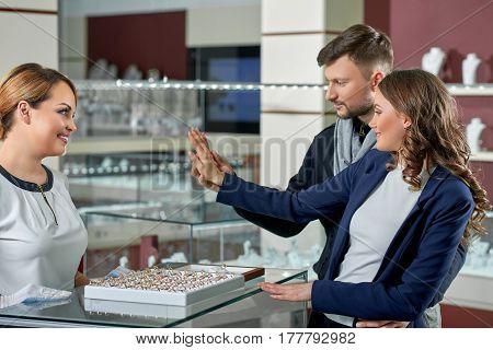 Fits perfectly. Shot of a happy young couple in love trying on engagement rings at the jewelry shop