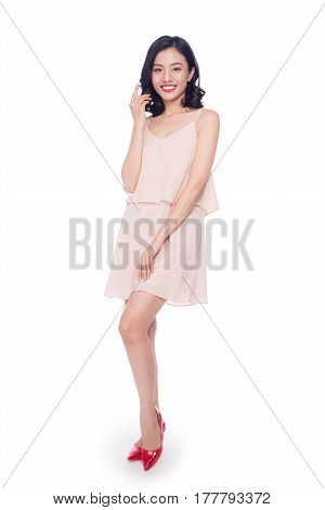 Beautiful happy cute asian woman in casual pink dress with red lips on white background
