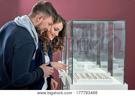 Aiming for the best one on display. Happy beautiful couple choosing an engagement ring on a display of a jewelry store