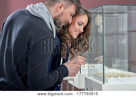 Such a hard choice here Bearded man and his beautiful smiling girlfriend shopping at the jewelry store