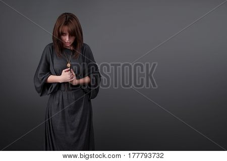 Portrait of a young caucasian woman praying. Prayer girl dressed in Vestments of a nun on gray studio background. Religion and hope concept.