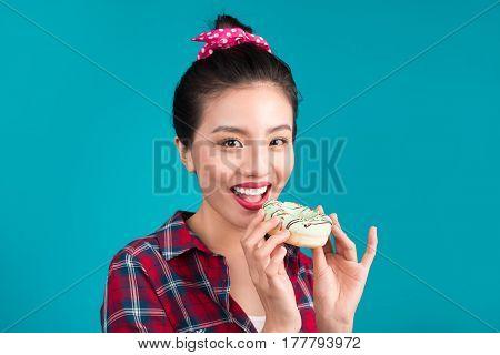 Retro joyful woman enjoy sweets dessert standing over blue background.