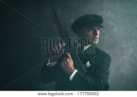 Retro 1920S English Gangster Wearing Flat Cap And Suit. Standing With Gun.