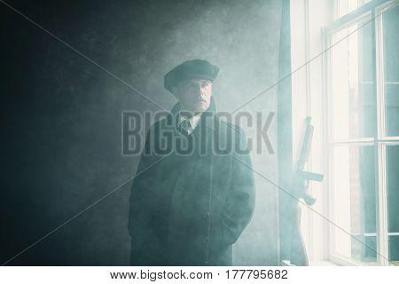 Retro 1920S English Gangster Wearing Flat Cap And Coat. Standing Near Window.