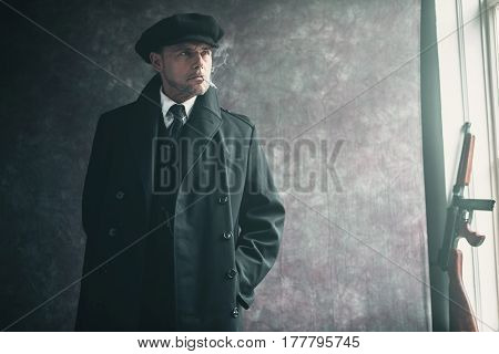 Retro 1920S English Gangster Smoking Cigarette. Wearing Black Coat And Flat Cap.