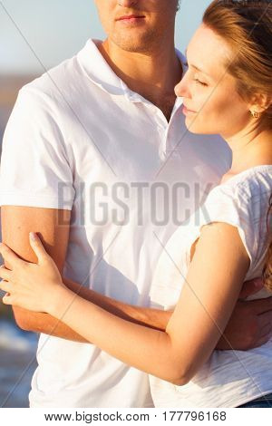 Attractive Young Couple Cuddling At The Beach. Close Up