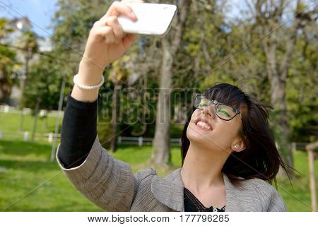 Cheerful woman taking selfie photo with mobile phone
