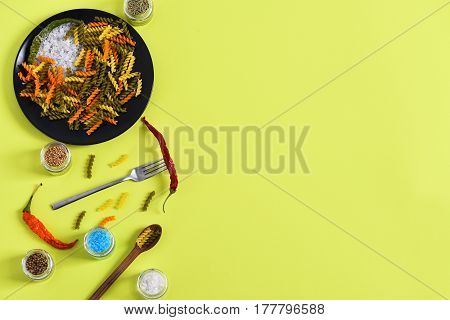 Colorful Dried Fusilli Pasta With Salt Crystals On Black Plate
