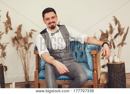 Elegant man in suit with bow tie smiling sitting in chair