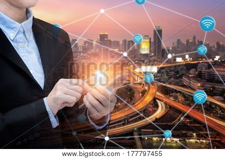 Asian business woman use smartphone technology for internet of things with Smart city with wifi connection.Photo design for smart city and smart technology internet of things concept