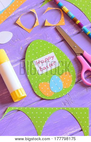 Happy Easter greeting card in egg shape. Materials and tools to promote creativity and creative learning in kids. Easter paper gift idea for kids. Vertical photo