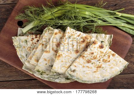 Scallion pancakes. Round unleavened flatbread minced green onions and dill. Top view.