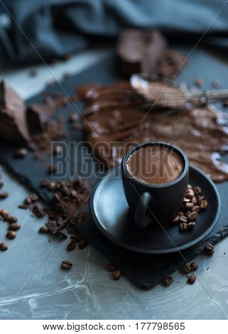Cup of hot chocolate. Close-up image of hot liquid chocolate and coffee beans