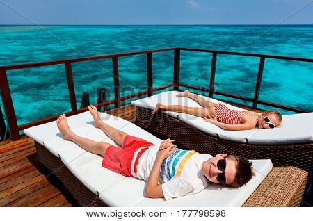 Kids enjoying tropical summer vacation relaxing at overwater villa in luxury resort