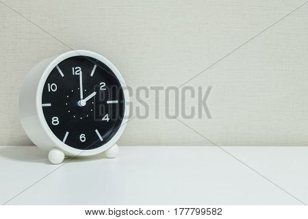 Closeup black and white alarm clock for decorate in 2 o'clock on white wood desk and cream wallpaper textured background with copy space