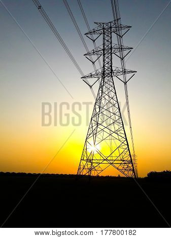 Electric high voltage power post at sunset.
