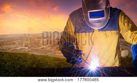 Double exposure welding worker welding steel structure with oil and gas refinery plant of petroleum or petrochemical industry production in background.