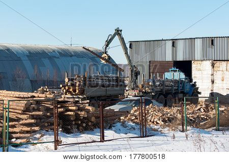 Loader loads logs into a timber truck in the warehouse