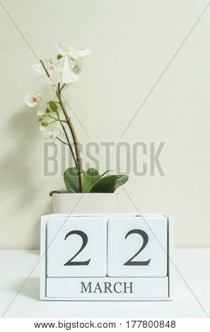Closeup white wooden calendar with black 22 march word with white orchid flower on white wood desk and cream color wallpaper in room textured background selective focus at the calendar